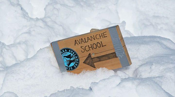 """En skyllt där det står """"Avalanche School"""" som sitter fast i snö."""