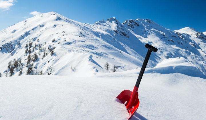 En röd lavinspade som står i snön framför snötäckta berg.
