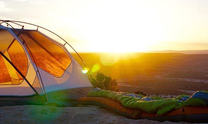 Ett tält och ett liggunderlag med en solnedgång i bakgrunden.