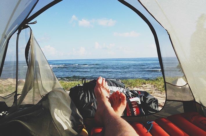 First person-vy från en person som ligger barfota på ett liggunderlag i ett tält. Med havet som utsikt.