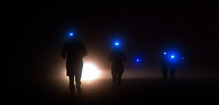 Personer som springer med pannlampa i mörkret.