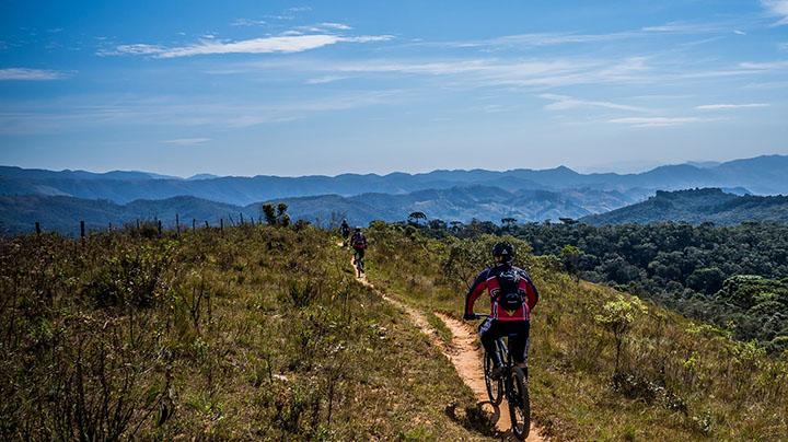 Tre personer som cyklar på mountainbike på en liten stig.