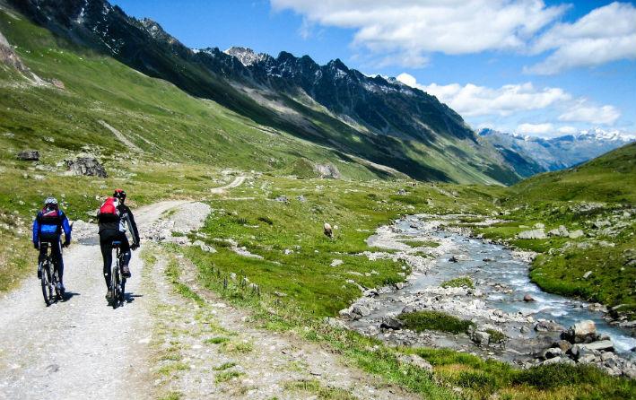 Två mountainbikecyklister som cyklar vid ett stort berg på en vacker dag.