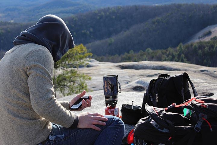 En person som kollar mobilen framför sin packning i vildmarken.