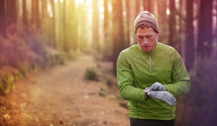 En person som kollar på sin pulsklocka under en löprunda i skogen.