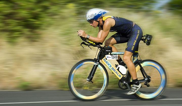 En man på en racercykel som cyklar på en väg.