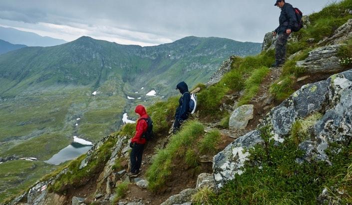 Tre vandrare som går ner för ett brant berg i dåligt väder.