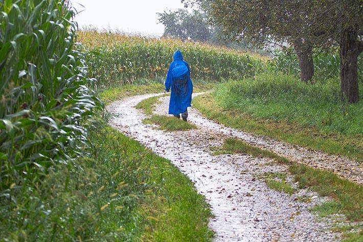 En person som går på en väg i spöregn.