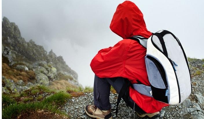 En person som sitter på huk och kollar ner för ett berg i dåligt väder.