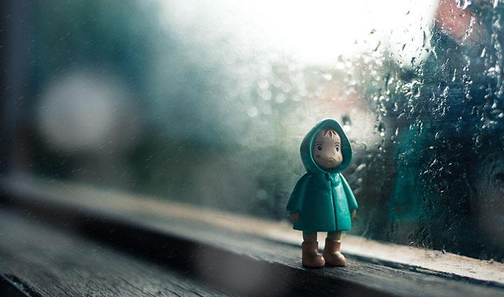 En liten docka med regnjacka som står vid ett fönster.