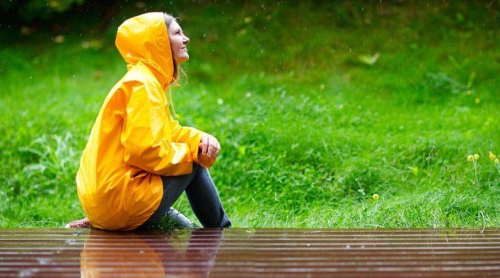 Kvinna som sitter ute i regnet med gul regnjacka på sig.