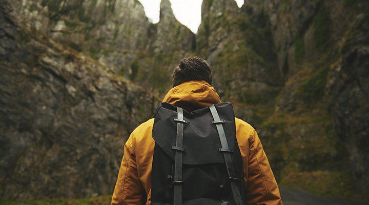 En person med ryggsäck som står ute i naturen framför ett berg.