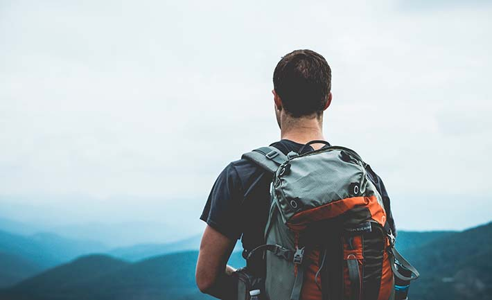 En man som står och kollar ut över lite kullar med en vandringsryggsäck på ryggen.