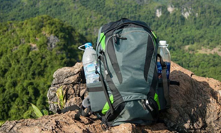 En vandringsryggsäck som ligger på ett berg och har två vattenflaskor i sidofacken.