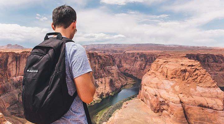 Man som står på grand canyon med ryggsäck.