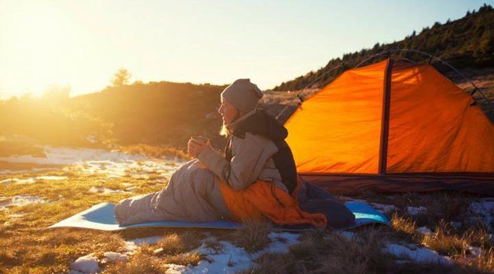 Person som sitter i en sovsäck utanför ett tält.