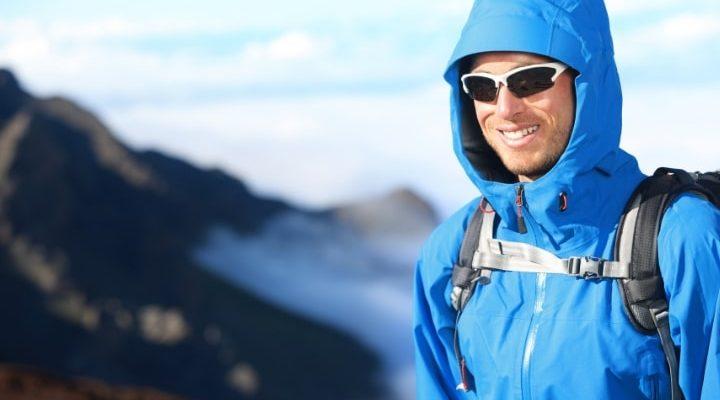En man som står ute i naturen med blå skaljacka.