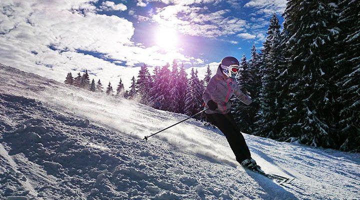 Person som åker skidor i en skidbacke, med skidjacka.