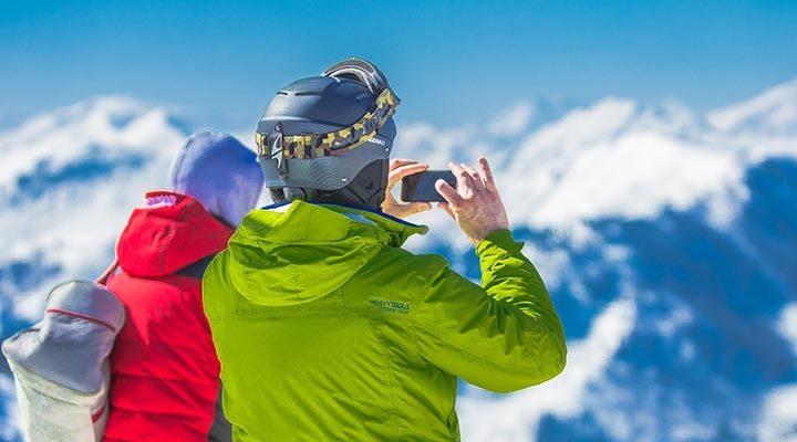 Två personer som står uppe vid ett stort berg. En av dom har en skidhjälm på sig.