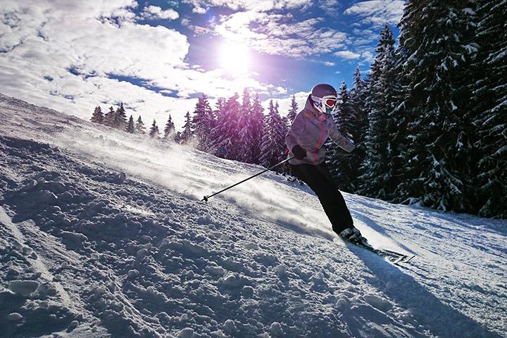 Person som åker skidor ner i en backe, har skidglasögon på sig.
