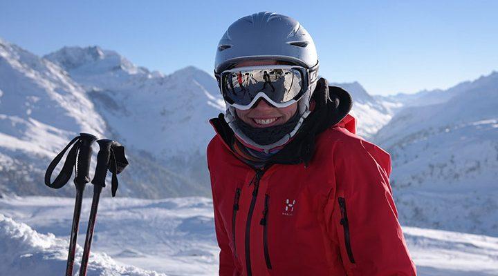 Person som står i vinterlandskap med skidglasögon.