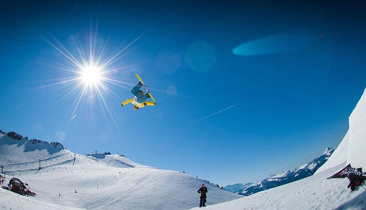 Person i snowboard-park som hoppar med en snowboard.