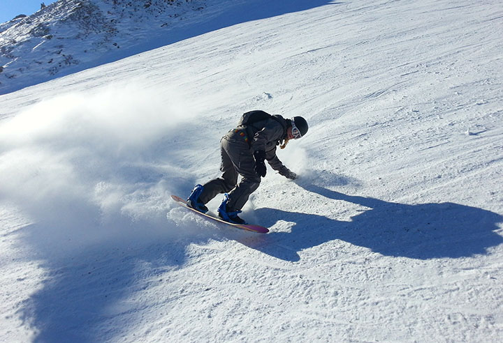 En person som åker i en backe på en snowboard.