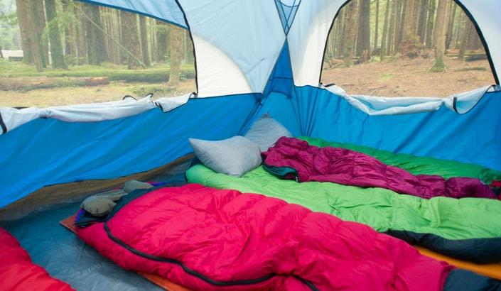Tre sovsäckar som ligger uppbäddade i ett tält.