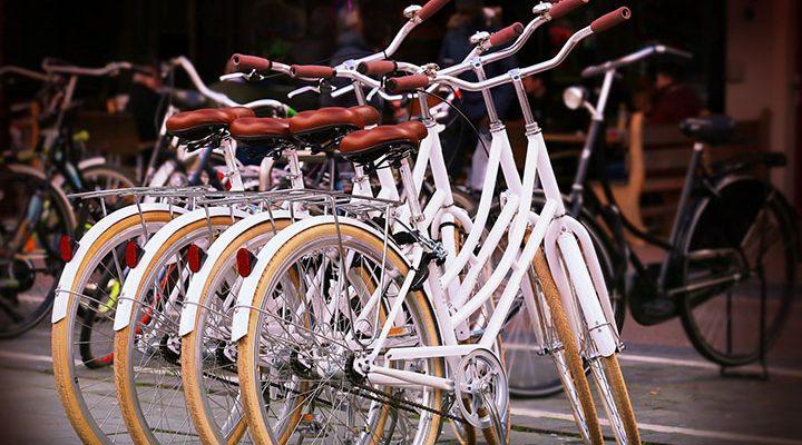 Vita stadscyklar som står på gatan.