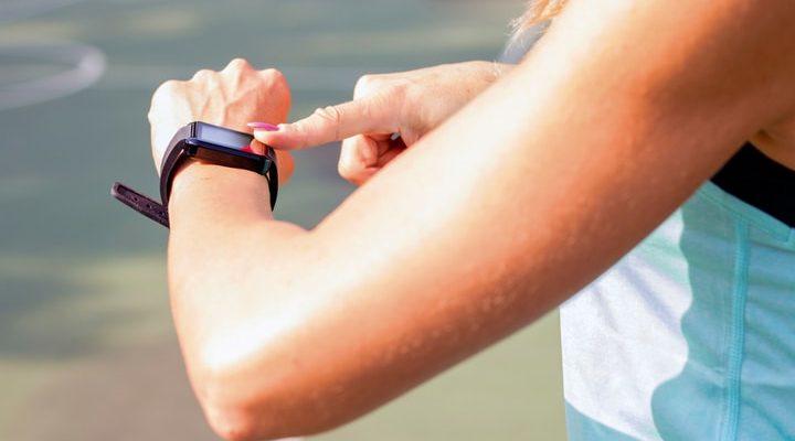 En kvinna kollar på stegräknaren på armen.