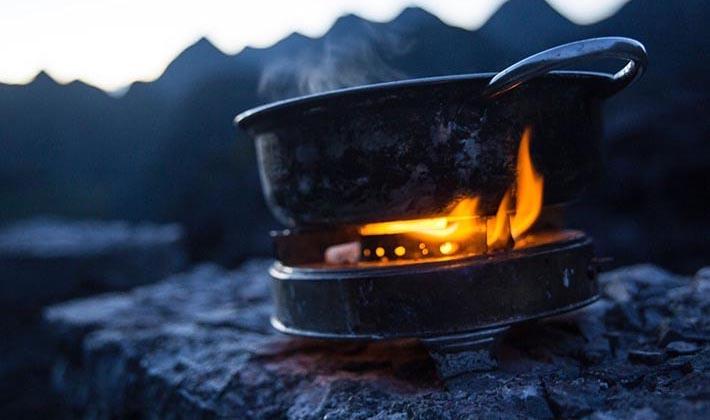 En gammal gasbrännare värmer mat i en kastrull.