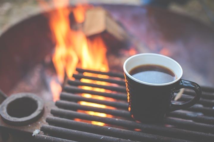 En kaffekopp som står framför en lägereld.