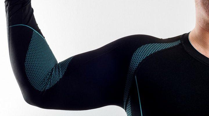 Armen på en person med blått och svart underställ på sig.