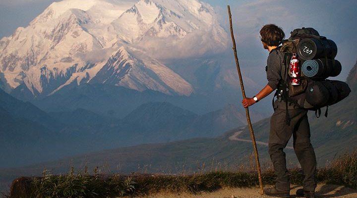 En man som står med vandringsutrustning vid en häftig utsikt.