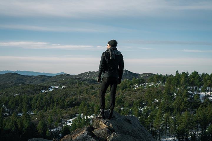 En person som står på ett berg med skog i bakgrunden och fin utsikt.