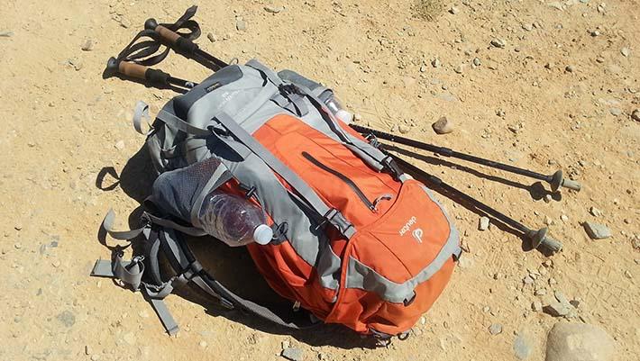 En vandringsryggsäck som ligger på marken bredvid ett par vandringsstavar. ee60f486fdc57