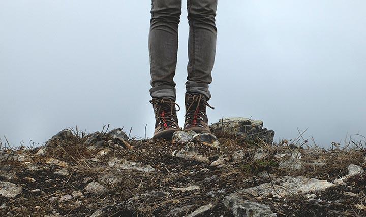 Två ben som står på en lite stenig kulle med två vandringskängor på fötterna.