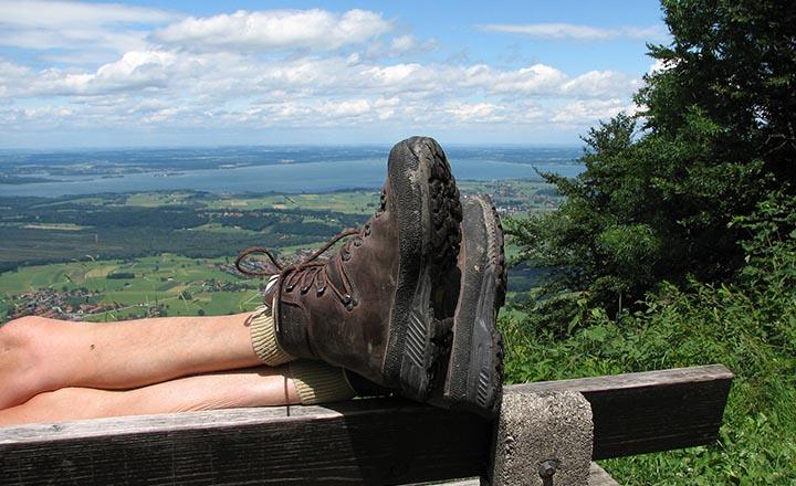 Benen från en person som har ett par vandringskängor på sig. Personen vilar benen mot en bänk på en plats med fin utsikt.