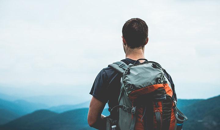 Man med ryggsäck som vandrar.