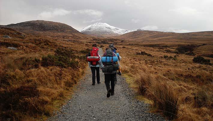 Tre personer som går på en vandringsled i lite grått och mulet väder. Alla har ryggsäckar på sig.