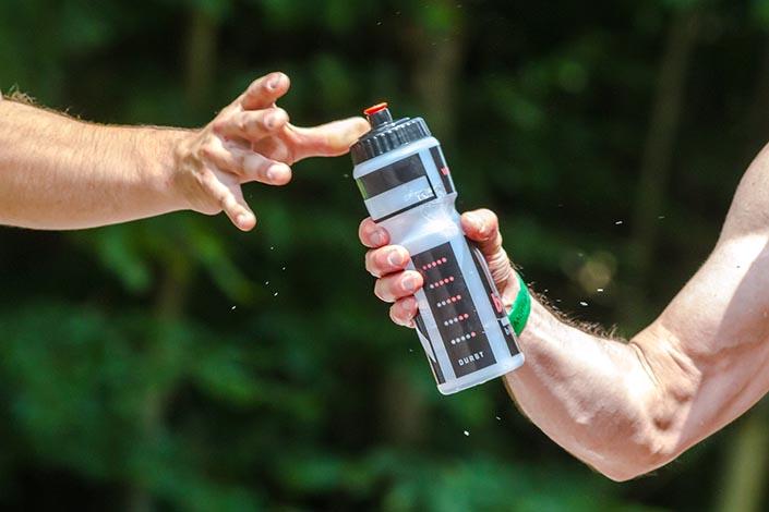 En hand som räcker en vattenflaska till en hand som ska ta emot den.