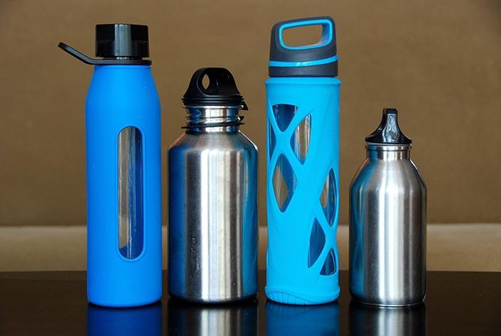 Fyra stycken vattenflaskor. Två i glas och två i rostfritt stål.